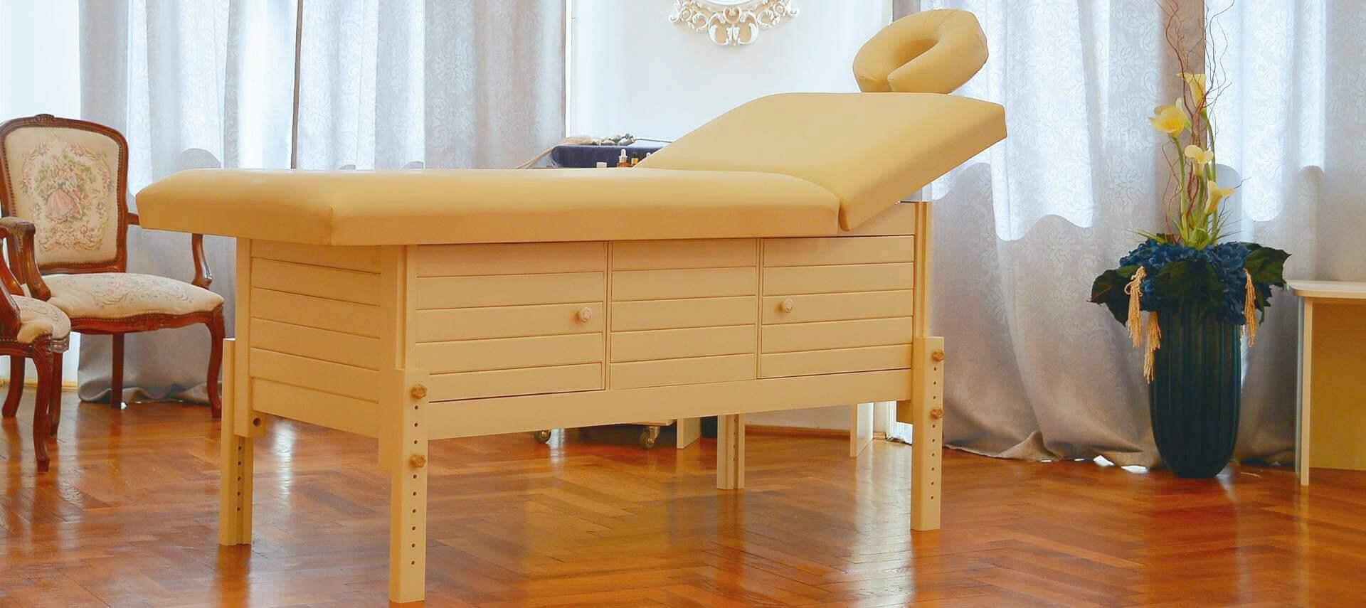 Masă de masaj staționară, model Aisha, de la BIOS, pernă patru secțiuni, tapițerie crem, finisaj lemn crem, spațiu de depozitare cu două uși batante.