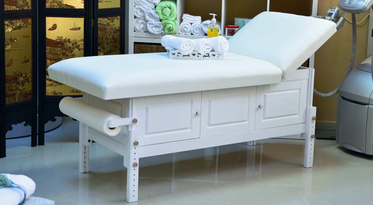 Masă de masaj staționară, model Bella, de la BIOS! Structura de lemn masiv finisată crem, pernă două secțiuni, tapițerie piele ecologică poliuretanică crem, spătar rabatabil, suport prosop hârtie ataşat
